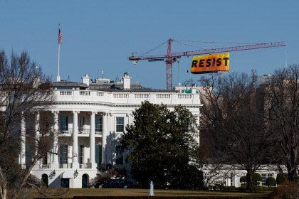WASHINGTON, DC - JANUARY 25: With the White House in the foreground, protesters unfurl a banner atop a crane at the construction site of the former Washington Post office building, January 25, 2017 in Washington, DC. The protestors are with the Greenpeace organization. (Photo by Drew Angerer/Getty Images)